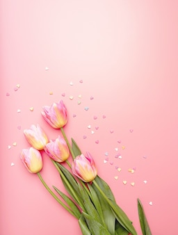 Pink and yellow tulips decorated with small heart shapes on pink background flat lay top view with copy space