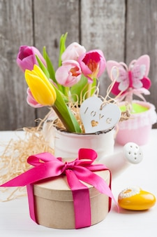 Pink yellow tulips on rustic wooden background