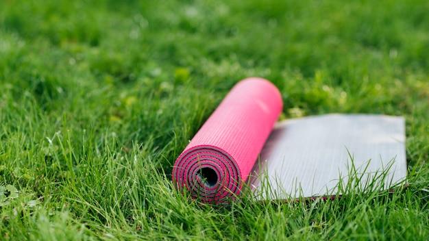 Розовый коврик для йоги на траве