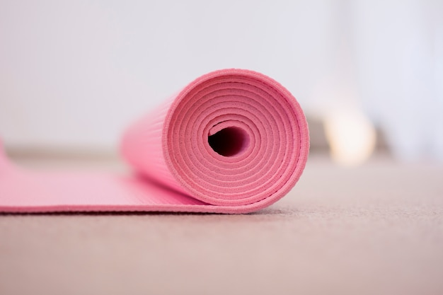 Pink yoga mat, rolled up.