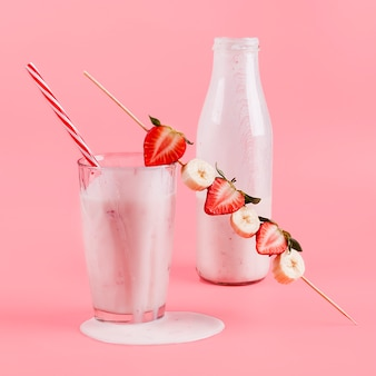 Pink yogurt in bottle and glass with berries
