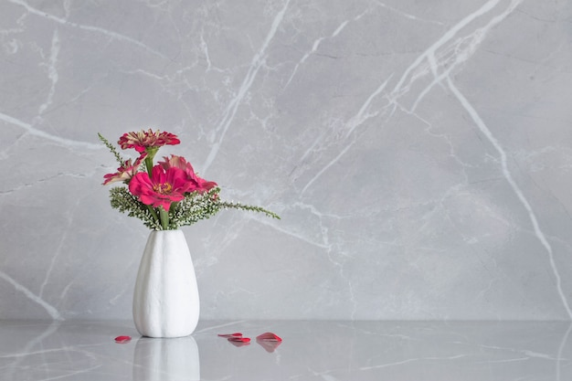 Розовые цветы циннии на вазе на мраморном фоне