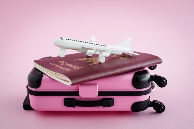 Pinky luggage with thai passport and white airplane model on pink background for travel and journey concept