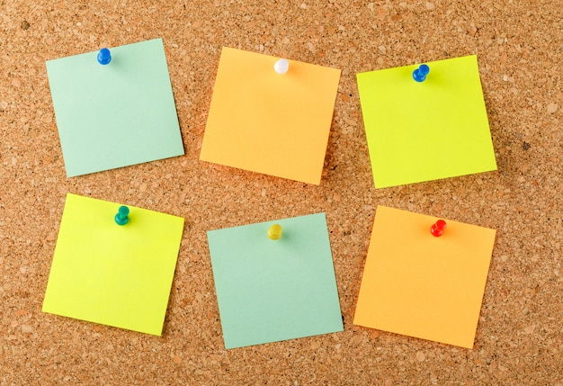 Pinned sticky notes on a light surface. flat lay.