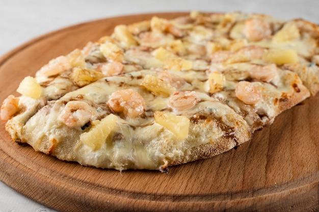 흰색 바탕에 나무 접시에 새우와 파인애플을 넣은 핀사 로마나. 해산물 스크루키아렐라.