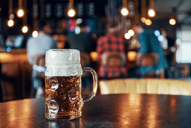 사람들과 술집에서 테이블에 거품 서와 차가운 신선한 맥주의 파인트 잔