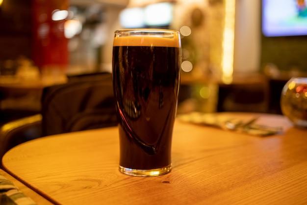 バーの木製テーブルの上に、泡の入った濃いスタウトビールのパイントグラスが立っています。