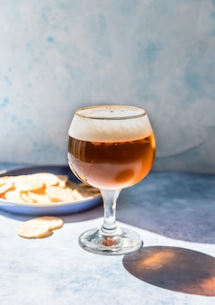 Пинта светлого пива в стакане с картофельными чипсами пиво и закуски