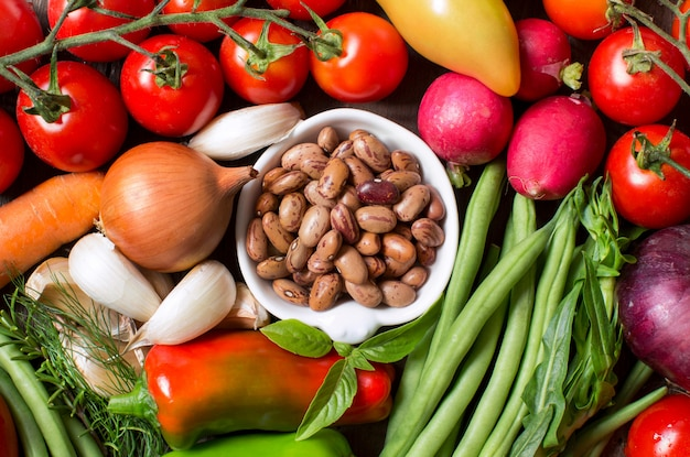 Pinto beans in a bowl with fresh vegetables top view