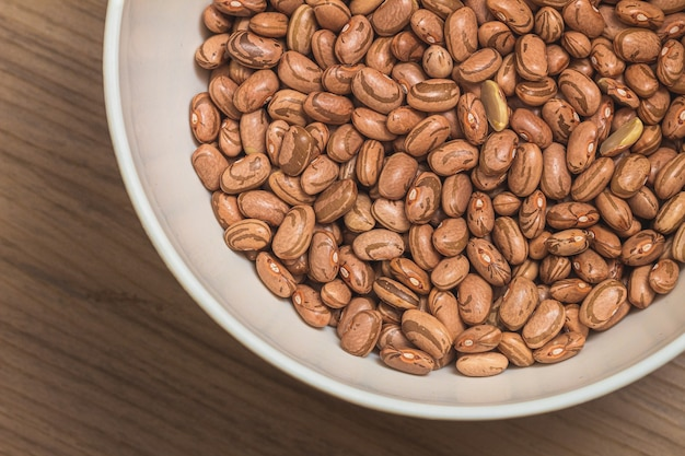 Pinto beans in a white bowl in closeup photo with top view