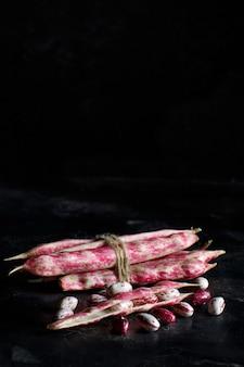 暗い背景にポッドを持つピント豆のクローズアップ