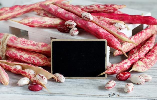 小さな黒板が付いている木製のテーブルの上のさやが付いているピント豆