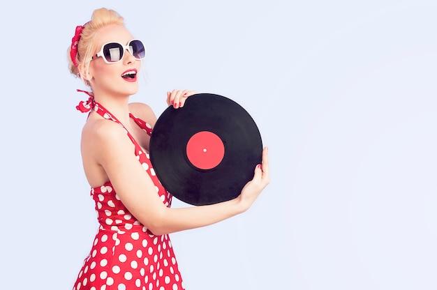 Очаровательная девушка в винтажном платье с виниловыми пластинками