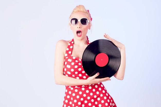 ビニールレコードを保持しているヴィンテージドレスのピンナップガール