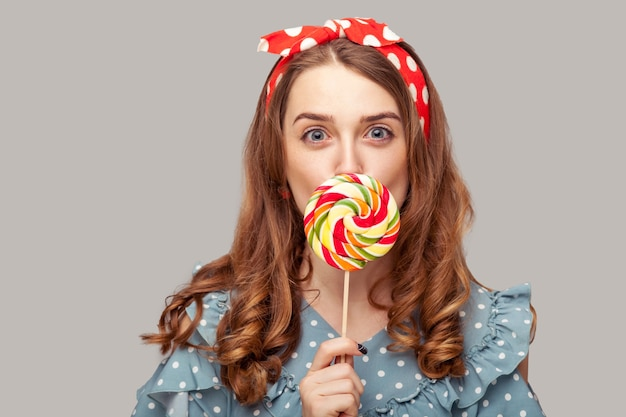 Pinup girl licking sweet candy looking eating delicious lollipop with surprised expression.