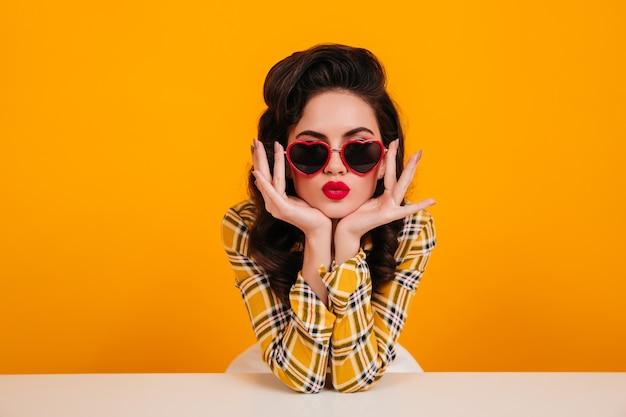 ハート型のメガネでポーズをとるピンナップガール。黄色の背景に座っている明るい化粧の素敵な女性。