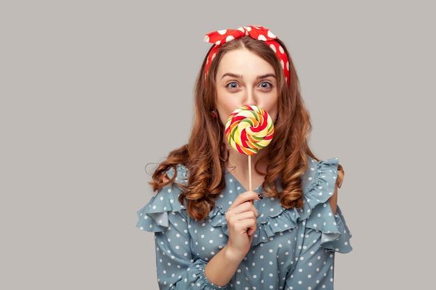 Pinup girl ruffle blouse licking sweet candy looking at camera