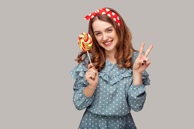 Pinup girl ruffle dress holding sweet spiral candy looking at camera, showing victory peace