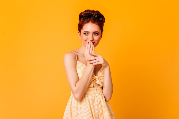 Очаровательная девушка улыбается и закрывает рот руками. студия сняла веселую имбирь с элегантной прической.