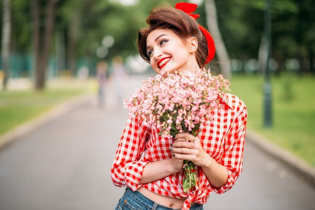 Pinup girl with bouquet of flowers, retro american fashion. cute smiling woman in pin up style