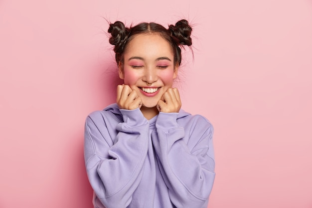 Pinup japanese woman with two combed hair buns touches cheeks, has smooth skin, wears vivid rosy makeup, piercing in nose, wears sweatshirt, smiles positively, isolated over pink background.
