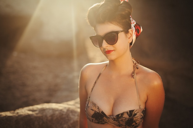 Pinup look dressed girl sitting on the rocks sexy woman with red sensual lips in swimsuit