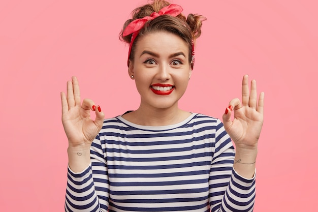 Pinup retro woman with make up, healthy skin, wears striped sweater and headband, has broad smile, makes okay gesture, shows that everything is good