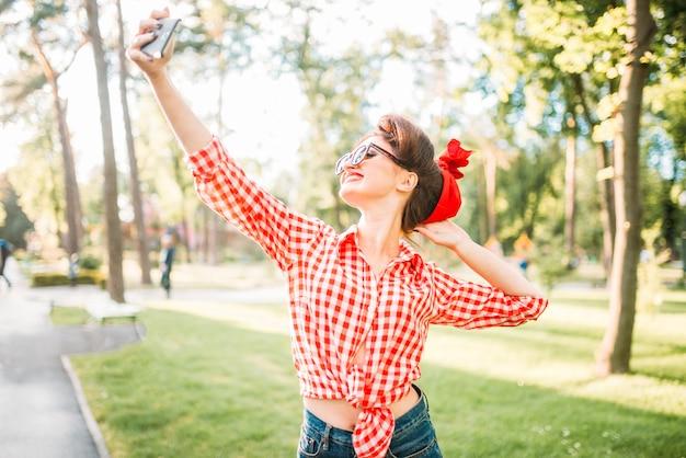 Очаровательная сексуальная дама делает селфи на камеру в парке