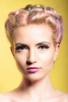 Pinup style portrait of a young beautiful woman with blue eyes and makeup. on a yellow background