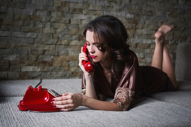 Девушка pinup с брюнетка волосы и ретро макияж с красными губами в халате на темном фоне. девушка лежит на кровати. старинное изображение. женщина разговаривает по телефону. дисковый телефон. ощущение грусти