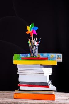 積み重ねられた本の風車と鉛筆の鍋、背景に黒板の質感を持つ白い机の上の学用品..学習、教育の概念