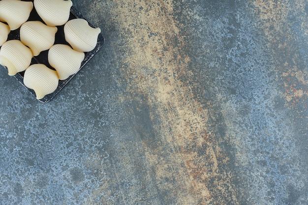 Condire le paste nel vassoio, sulla superficie di marmo.