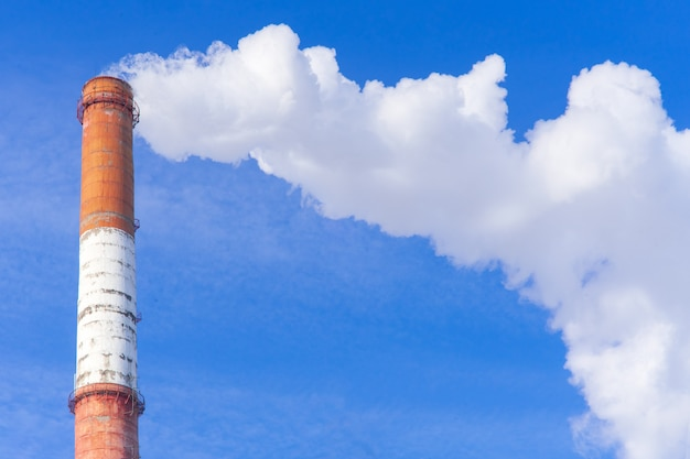 The pipe of the plant emits harmful substances into the atmosphere. close-up on a sky background.
