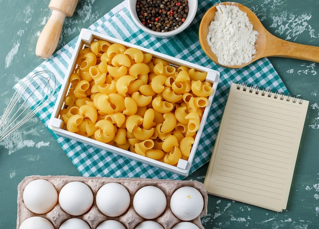 Pipe rigate pasta in a box with eggs, peppercorns, starch, rolling pin, whisk and copybook