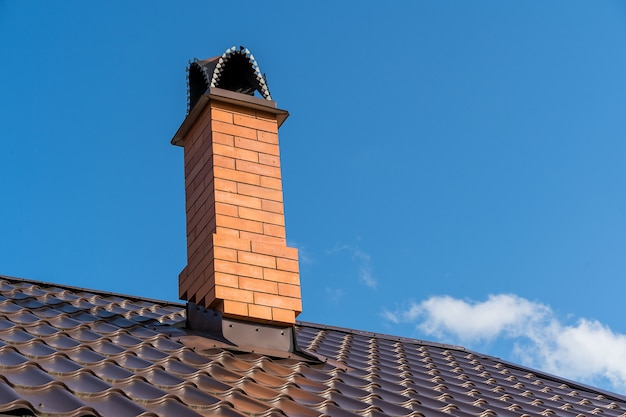 The pipe on the roof of country house under blue sky