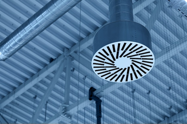 Pipe of supply and exhaust ventilation system on ceiling of commercial room or warehouse.