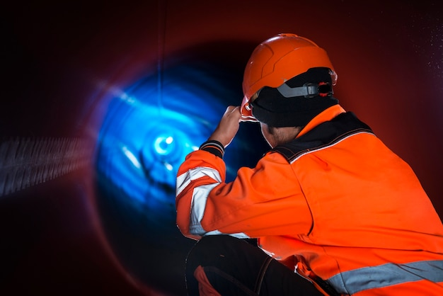Pipeline construction worker in reflective protective uniform inspecting pipe tube for natural gas distribution