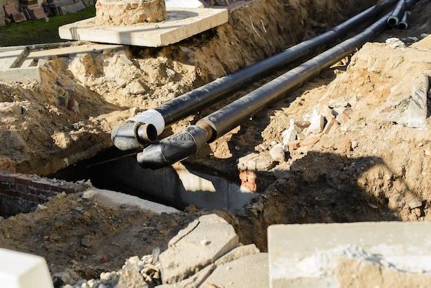 Ремонт трубопроводов, прокладка новых труб под землей. селективный акцент на переднем плане черных труб.