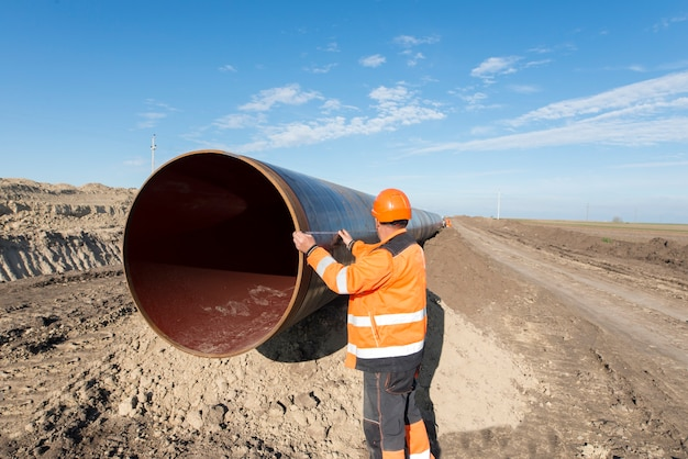 Pipeline workers measuring tube length for construction of gas and oil pipes