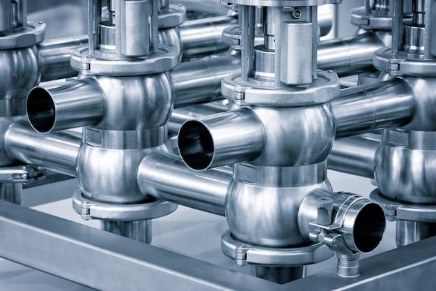 Трубопроводы из нержавеющей стали, системы перекачки жидкости или молока для пищевой промышленности. абстрактный промышленный фон.