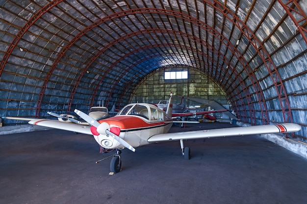 The piper cherokee plane is in a large garage for airplanes. a small private airfield with different planes. private aviation