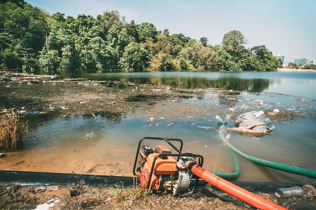 더러운 도시 연못에서 취수용 파이프. 도시에서 호수의 오염입니다. 물에 버리십시오.
