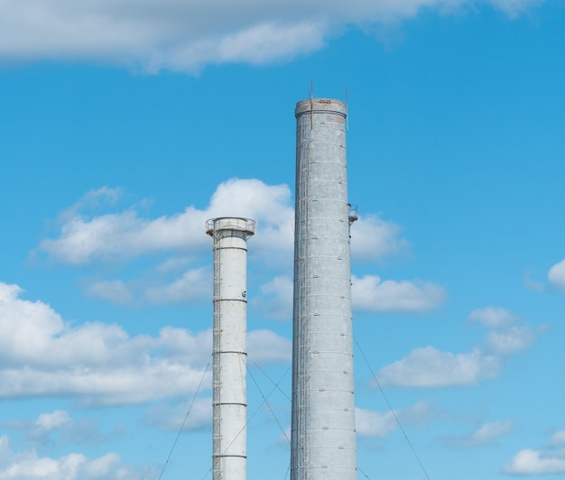 Трубы промышленного предприятия против голубого неба с облаками. дымоход без дыма