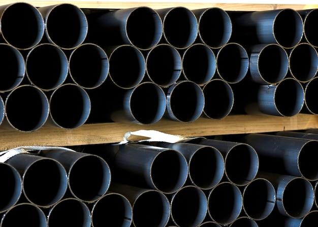 Железные трубы уложены на складе на большие куски дерева