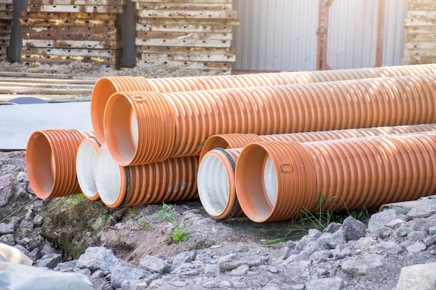 Трубы пластиковые гофрированные большого диаметра красного и оранжевого цвета для строительства.