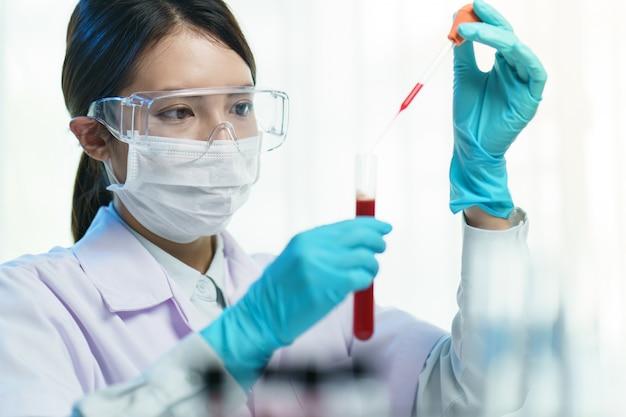試験管に液体を加えるピペット。血液サンプルを分析する研究助手。