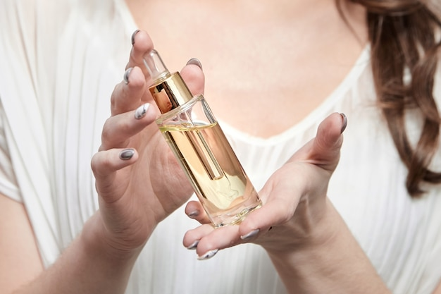 女性の手に化粧品オイルのピペットボトル