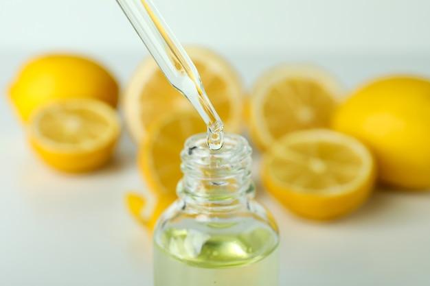 Pipette dripping oil in bottle against fresh lemons