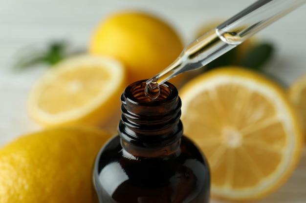신선한 레몬에 대한 병에 피펫 떨어지는 기름
