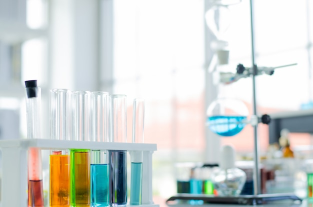 A pipette dropping sample into a test tube, abstract science background